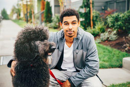 Mixed race man petting dog on sidewalk